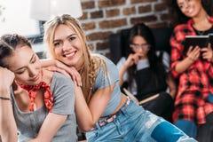Jeunes femmes ayant l'amusement ainsi que des livres de lecture d'amis derrière Photos libres de droits