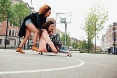 Jeunes femmes ayant l'amusement ainsi que la planche à roulettes Photo libre de droits