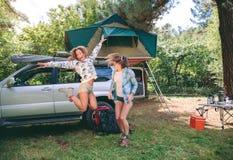 Jeunes femmes ayant l'amusement dans le terrain de camping avec 4x4 dessus Images libres de droits