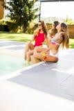 Jeunes femmes ayant l'amusement par la piscine Image libre de droits