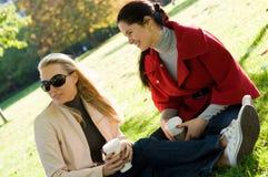 Jeunes femmes ayant la pause-café ensemble dans le stationnement Photos stock