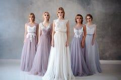 Jeunes femmes blondes de jeune mariée dans une robe de mariage moderne de couleur avec la coiffure élégante et composer Compositi photographie stock