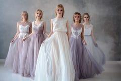 Jeunes femmes blondes de jeune mariée dans une robe de mariage moderne de couleur avec la coiffure élégante et composer Compositi photos stock