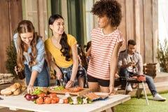 Jeunes femmes buvant de la bière et coupant des légumes tandis qu'hommes grillant la viande Photographie stock libre de droits