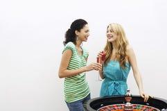 Jeunes femmes buvant des cocktails par la roue de roulette cultivée Images stock