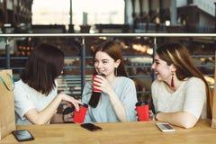 Jeunes femmes buvant du café au café dans le mail Images libres de droits