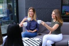 Jeunes femmes buvant du café au café et au repos Image libre de droits