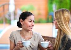 Jeunes femmes buvant du café dans un café dehors Images stock