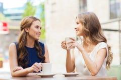 Jeunes femmes buvant du café et parlant au café Photos stock