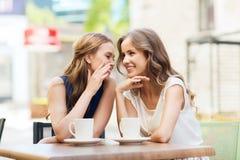 Jeunes femmes buvant du café et parlant au café Image stock