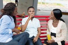 Jeunes femmes buvant du jus observé par ses amis Photos stock
