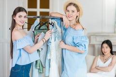 Jeunes femmes choisissant des vêtements ensemble à l'intérieur Image stock