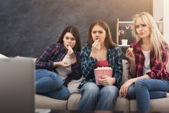 Jeunes femmes concentrées observant le film à la maison Images libres de droits
