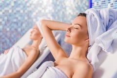 jeunes femmes couvertes de serviettes détendant sur des lits pliants Image libre de droits
