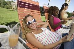 Jeunes femmes détendant sur la chaise de plate-forme Image libre de droits