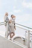 Jeunes femmes d'affaires avec les tasses de café jetables abaissant des escaliers contre le ciel Photos libres de droits