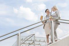 Jeunes femmes d'affaires avec les tasses de café jetables se tenant prêt la balustrade contre le ciel Photographie stock libre de droits