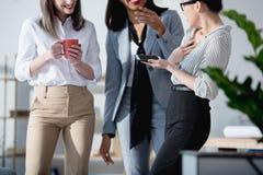 Jeunes femmes d'affaires multi-ethniques buvant du café et parlant au bureau Image libre de droits