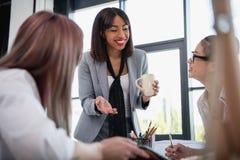 Jeunes femmes d'affaires parlant et buvant du café dans le bureau Photo stock