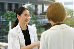 Jeunes femmes d'affaires saluant avec le visage de sourire, réunion de négociation d'affaires Photos libres de droits