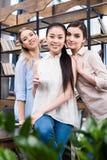 Jeunes femmes d'affaires se tenant ensemble et souriant tout en buvant du café sur le lieu de travail Images libres de droits