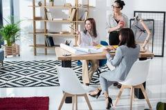 Jeunes femmes d'affaires travaillant avec des modèles et discutant le nouveau projet Image stock