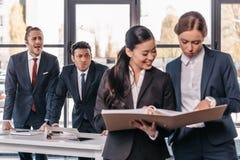 Jeunes femmes d'affaires travaillant ensemble tandis qu'hommes d'affaires grimaçant derrière Photographie stock libre de droits