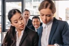 Jeunes femmes d'affaires travaillant ensemble tandis qu'hommes d'affaires grimaçant derrière Images stock