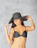 Jeunes femmes d'une chevelure noires posant dans le studio sur le gris Photos stock