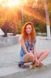 Jeunes femmes d'une chevelure rouges s'asseyant sur la planche à roulettes avec Photos stock