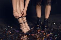 Jeunes femmes dans des chaussures élégantes se tenant sur les confettis brillants Photographie stock