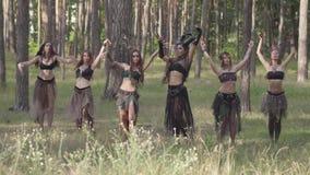 Jeunes femmes dans des costumes théâtraux des habitants ou des diables de forêt dansant dans la représentation d'apparence de for banque de vidéos