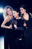 Jeunes femmes dans des robes élégantes faisant la fête et buvant du champagne ensemble images stock