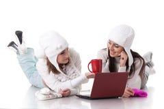 Jeunes femmes dans des vêtements de l'hiver avec l'ordinateur portatif Photographie stock
