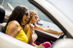Jeunes femmes dans la conduite blanche de cabriolet partout et le lookin images stock