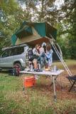 Jeunes femmes dans la couverture d'emballage de terrain de camping à l'intérieur du sac à dos Images stock