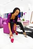 Jeunes femmes de couleur essayant sur les chaussures courantes neuves Image stock