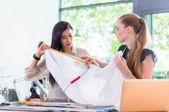 Jeunes femmes de couturier mesurant le tissu Photos libres de droits