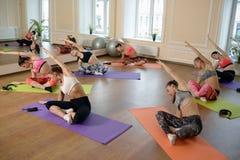 Jeunes femmes de groupe s'étirant et yoga de pratiques Photos stock