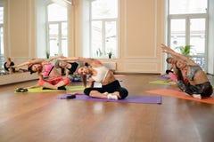 Jeunes femmes de groupe s'étirant et yoga de pratiques Images stock