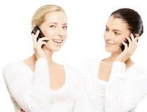 Jeunes femmes de sourire avec des smartphones Images stock
