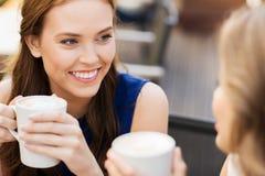Jeunes femmes de sourire avec des tasses de café au café Images libres de droits