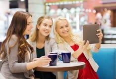 Jeunes femmes de sourire avec les tasses et le PC de comprimé Image stock