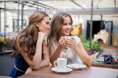 Jeunes femmes de sourire buvant du café au café de rue Images libres de droits