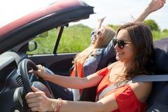 Jeunes femmes de sourire conduisant dans la voiture de cabriolet Image libre de droits