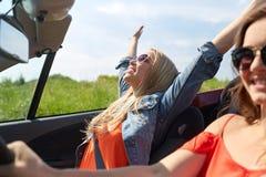 Jeunes femmes de sourire conduisant dans la voiture de cabriolet Photos stock
