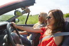 Jeunes femmes de sourire conduisant dans la voiture de cabriolet Photographie stock