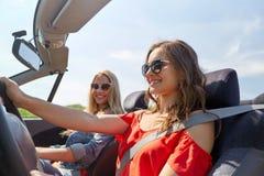 Jeunes femmes de sourire conduisant dans la voiture de cabriolet Photographie stock libre de droits