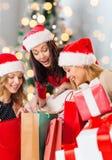 Jeunes femmes de sourire dans des chapeaux de Santa avec des cadeaux Photographie stock