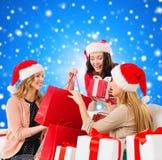 Jeunes femmes de sourire dans des chapeaux de Santa avec des cadeaux Image libre de droits